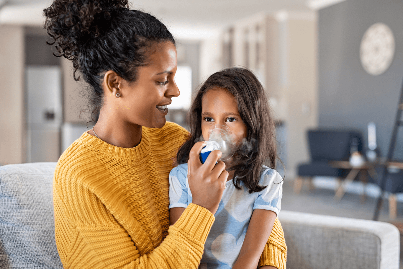 Mother helping her daughter use her nebulizer