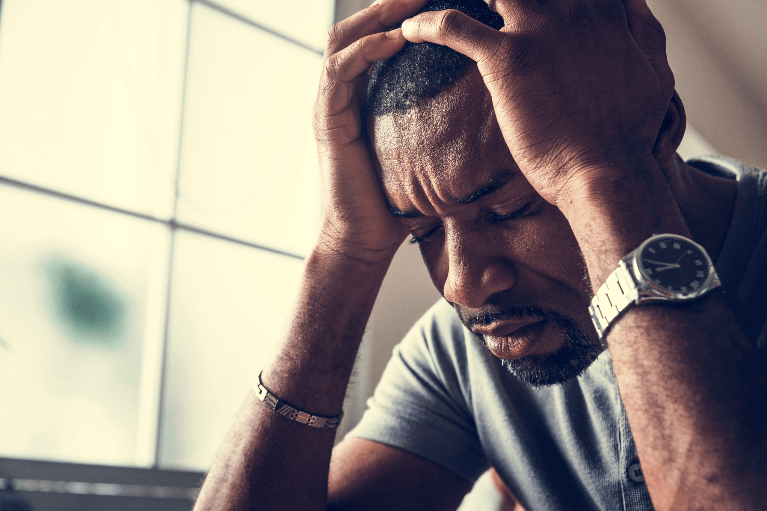 Depressed man holding his head with both hands